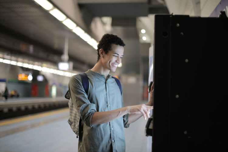 cheerful ethnic man using ticketing machine at subway station