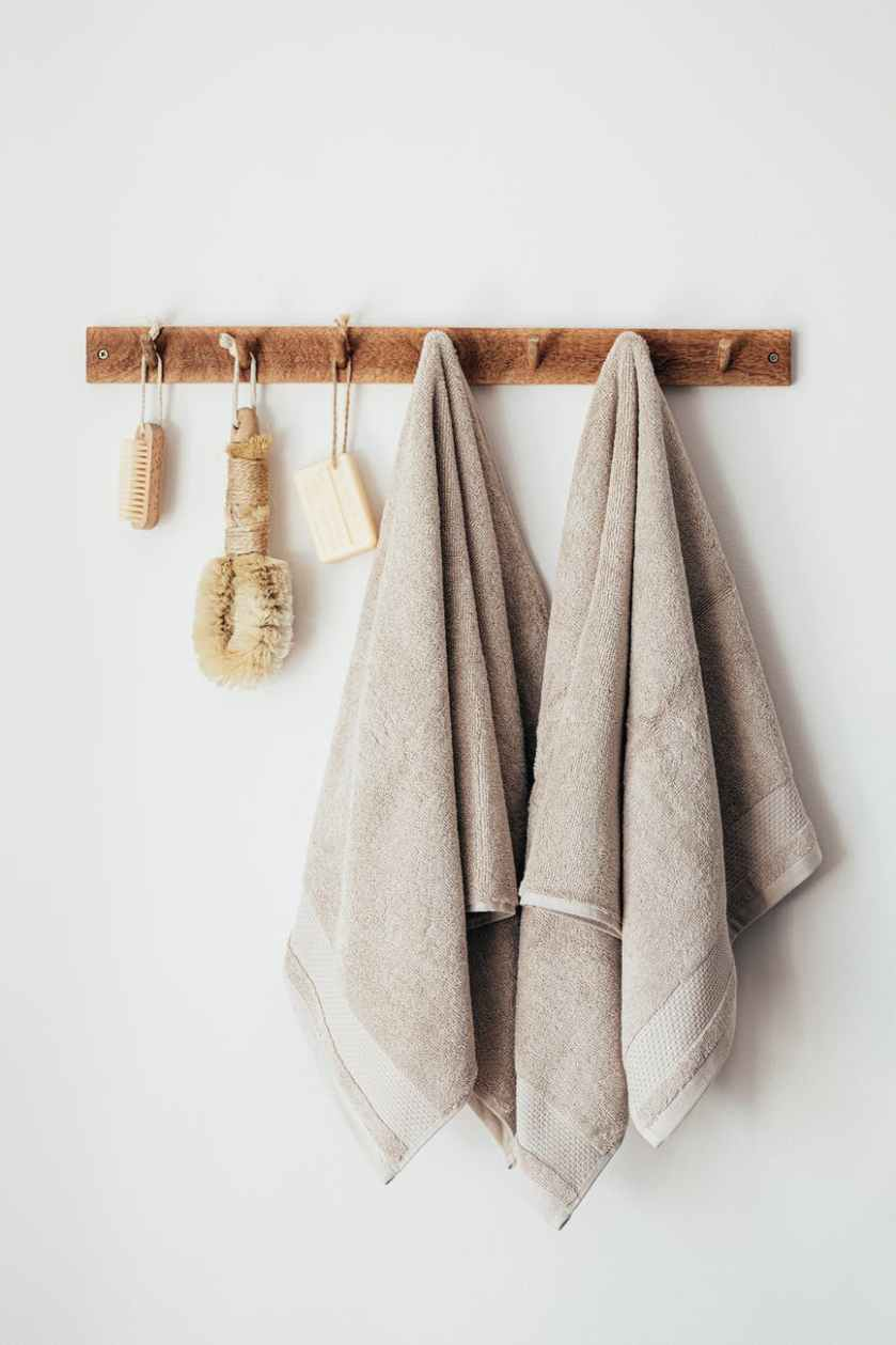wooden hanger with towels and natural bathroom tools